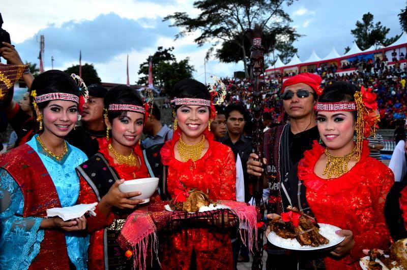 """Thompson Hs mit Sonnenbrille und traditionellem Zeremonienstab der Batak umgeben von jungen Damen in der moderner Bataktracht """"Kebaya""""."""